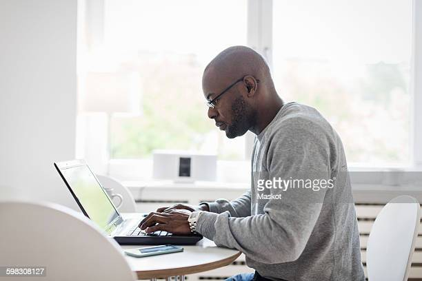Side view of man using laptop at table in house