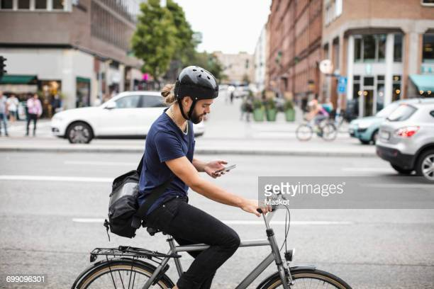 Side view of man using mobile phone while riding bicycle on city street