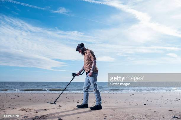 side view of man using recreational metal detector at horsey beach against sky - searching stock photos and pictures