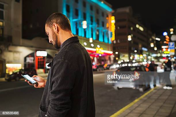 Side view of man using smart phone on city street at night