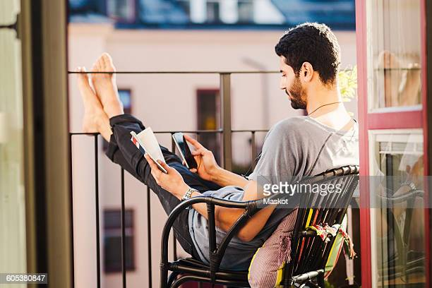 Side view of man using smart phone while holding guidebook at balcony