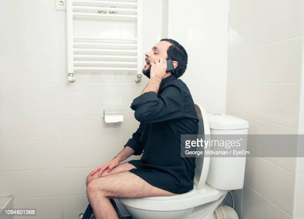 side view of man using smart phone while sitting on toilet seat - men taking a dump stock pictures, royalty-free photos & images