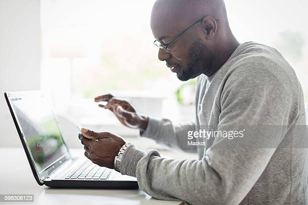 Side view of man using smart phone with laptop at table
