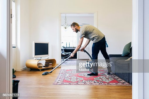 Side View Of Man Vacuuming Hardwood Floor Stock Photo Getty Images