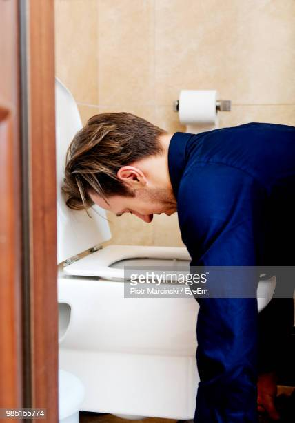 side view of man vomiting in toilet bowl at bathroom - toilet bowl stock photos and pictures