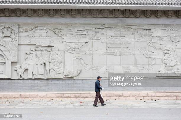 side view of man walking against carvings on wall - beijing stock pictures, royalty-free photos & images