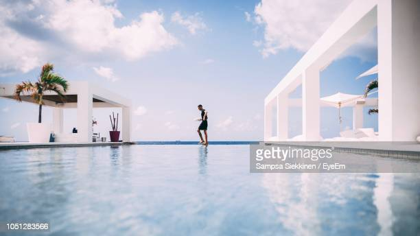side view of man walking at infinity pool against cloudy sky - infinity pool foto e immagini stock