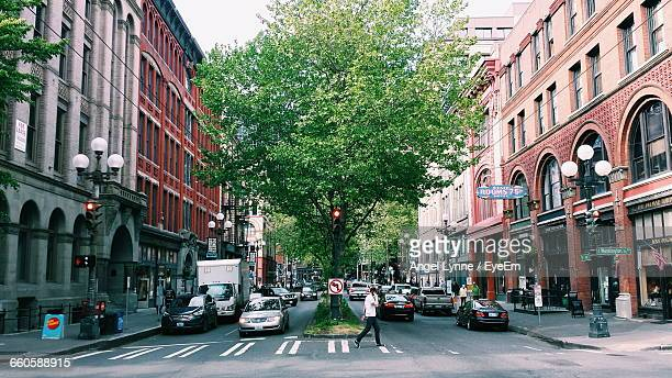 side view of man walking by cars on street in city - seattle stock pictures, royalty-free photos & images