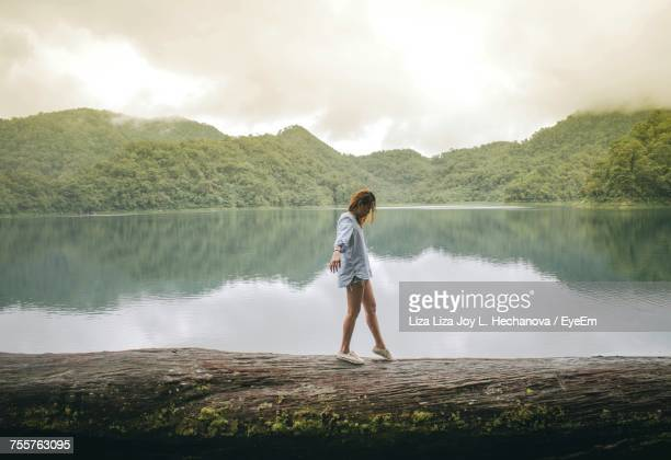 side view of man walking by lake against sky - beautiful filipino women stock photos and pictures
