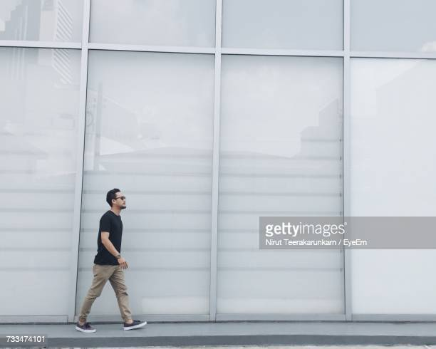Side View Of Man Walking On Footpath By Building