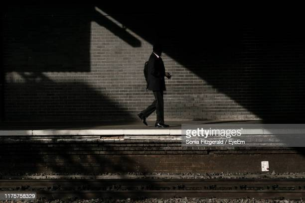 side view of man walking on railroad station platform - station stock pictures, royalty-free photos & images