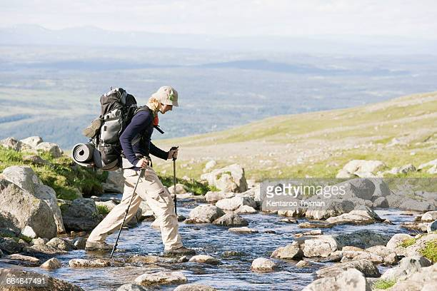 Side view of man walking on stones in stream