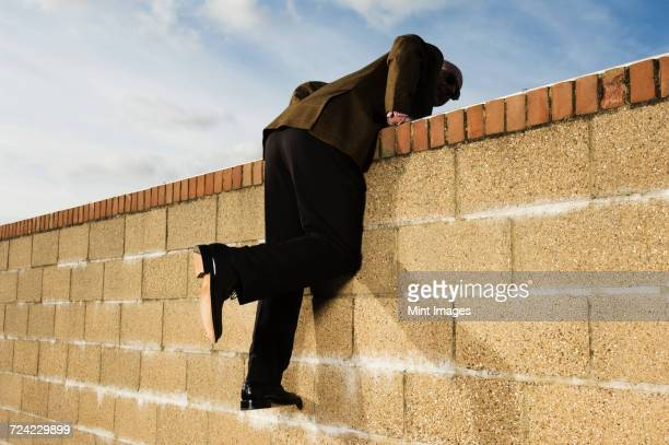 side view of man wearing a suit climbing over yellow brick wall. - のぼり ストックフォトと画像
