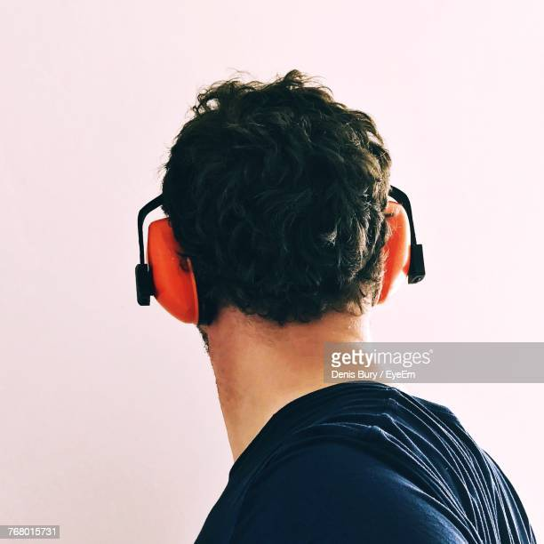Side View Of Man Wearing Ear Muff Against White Background