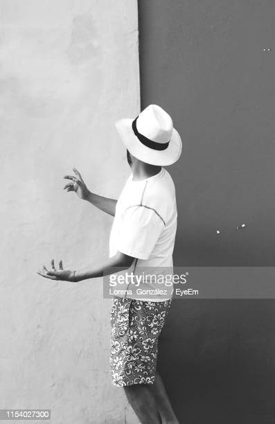 side view of man wearing hat while standing by wall - lorena cartagena stock photos and pictures