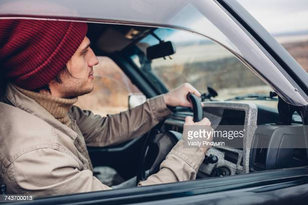 Side view of man wearing knit hat riding sport utility vehicle