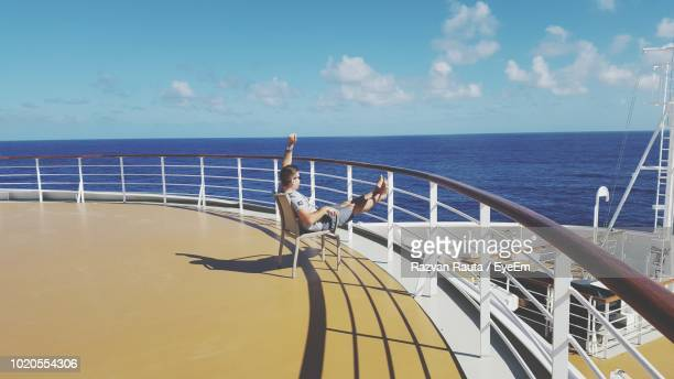 side view of man with arms raised sitting on cruise ship sailing in sea - kreuzfahrtschiff stock-fotos und bilder