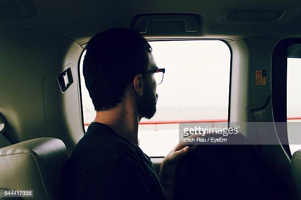 Side View Of Man With Eyeglasses Sitting In Car Looking Outside Window