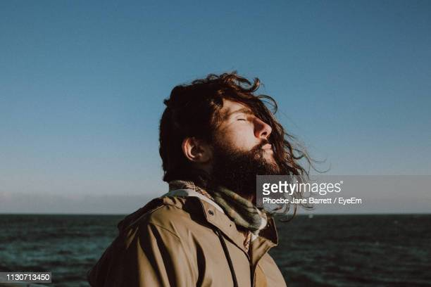 side view of man with eyes closed at beach against sky - cleveland stock pictures, royalty-free photos & images