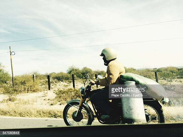 Side View Of Man With Milk Canister Riding Motorcycle On Road