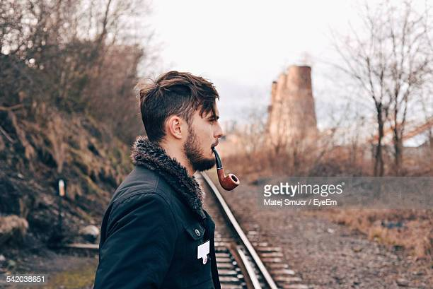 Side View Of Man With Smoking Pipe On Railroad Track