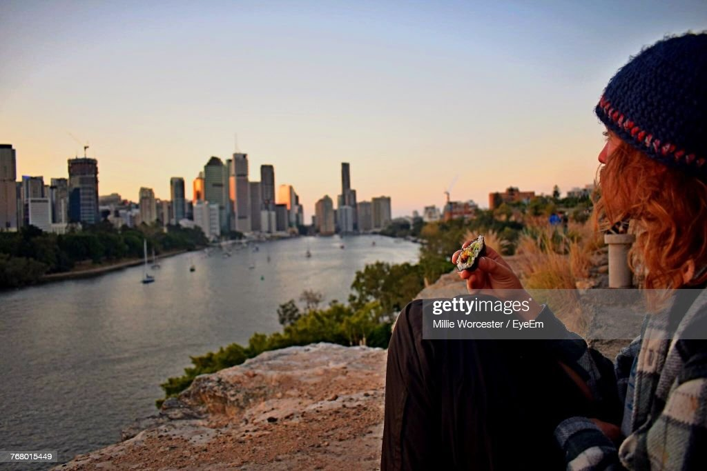 Side View Of Man With Sushi Sitting On Cliff By River : Stock Photo