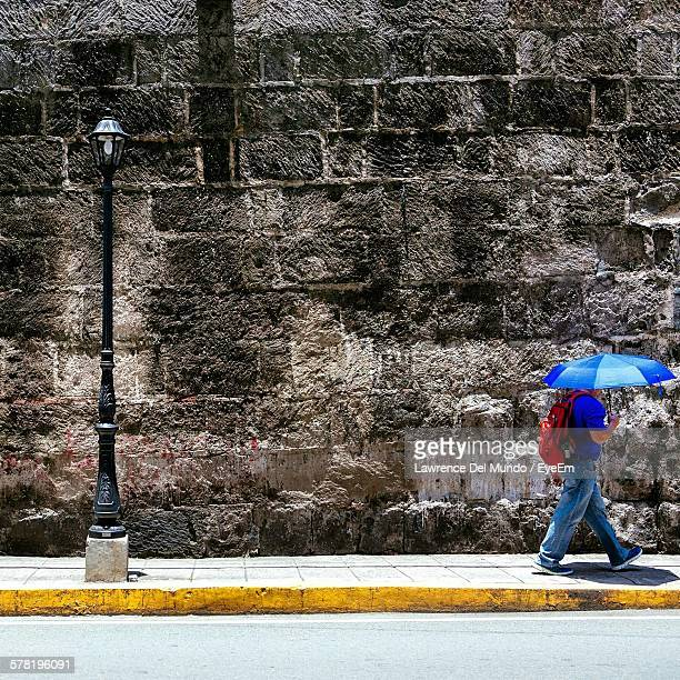 side view of man with umbrella walking on sidewalk during sunny day - old manila stock pictures, royalty-free photos & images