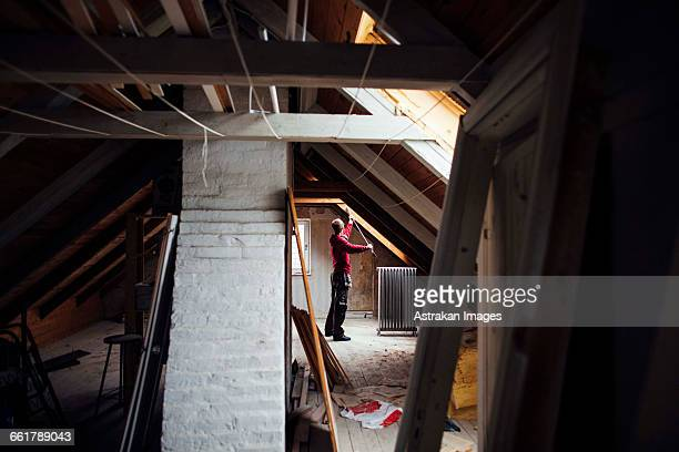 Side view of man working in attic under construction
