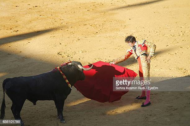 Side View Of Matador Showing Red Cape With Black Bull On Field