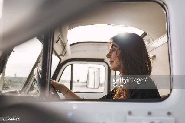 Side view of mature businesswoman driving portable office truck