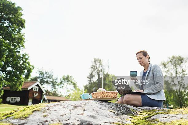 Side view of mature businesswoman having coffee while using laptop on rock