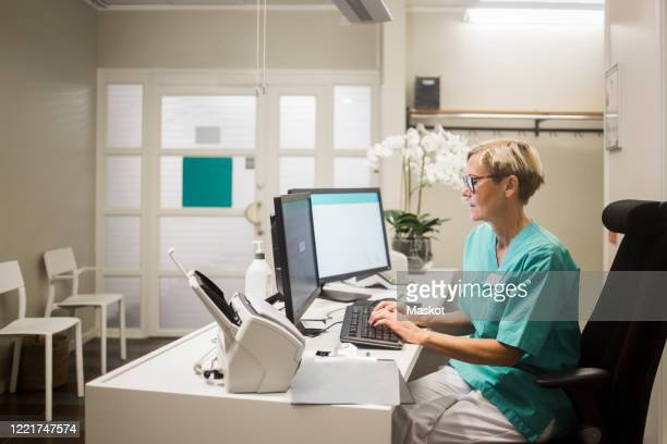 side view of mature female doctor working over computer while sitting in clinic - medical receptionist uniforms stock pictures, royalty-free photos & images