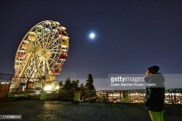 side view of mature man looking at illuminated ferris wheel against sky - tibidabo stock pictures, royalty-free photos & images
