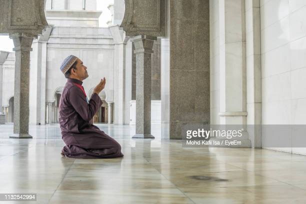 side view of mature man praying while kneeling at mosque - muslim praying stock pictures, royalty-free photos & images