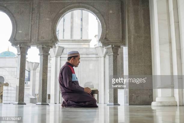side view of mature man reading koran while kneeling at mosque - koran stock pictures, royalty-free photos & images
