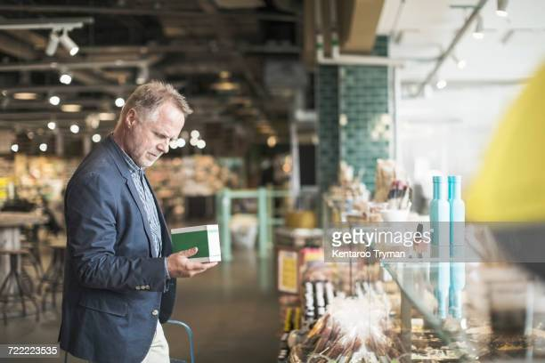 Side view of mature man reading label on food package in supermarket