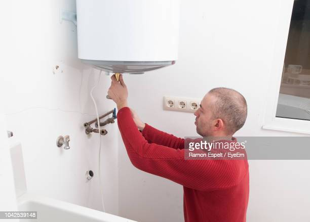 side view of mature man repairing water heater against wall in bathroom - boiler stock pictures, royalty-free photos & images