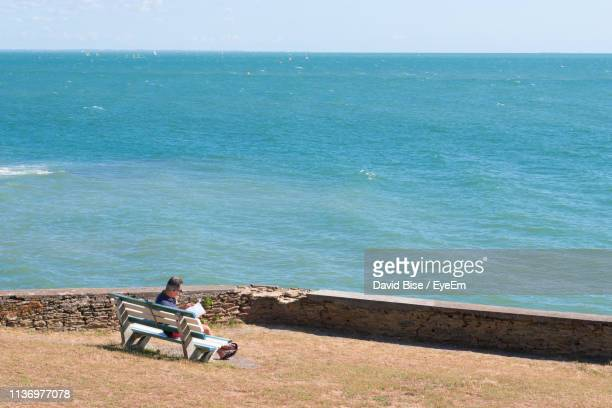 side view of mature man sitting on bench against sea during sunny day - terrasse panoramique photos et images de collection