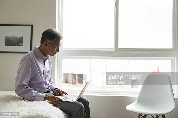 Side view of mature man sitting on edge of bed using laptop