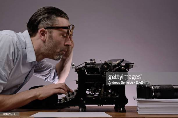 Side View Of Mature Man Using Typewriter On Table Against Wall At Office