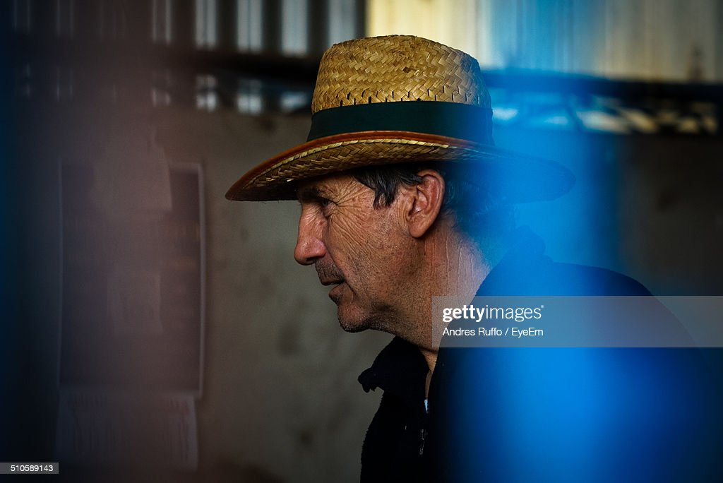 Side view of mature man wearing straw hat : Stock Photo