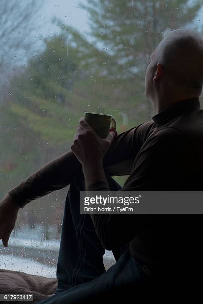 side view of mature man with coffee sitting on window sill - brian sills stock pictures, royalty-free photos & images