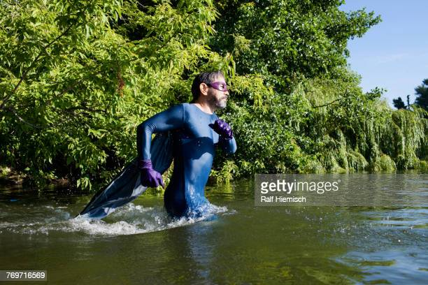 side view of mature superhero running in river against trees - wading stock pictures, royalty-free photos & images