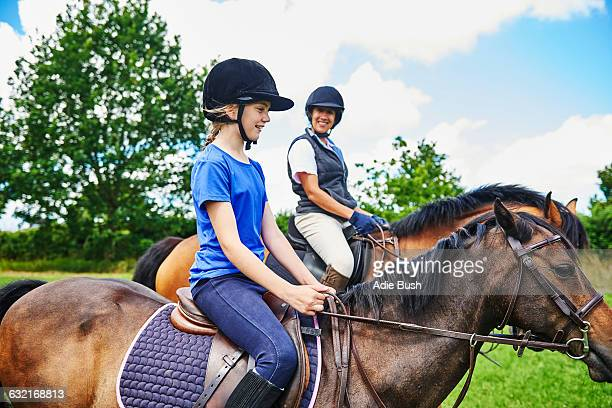 side view of mature woman and girl on horseback wearing riding hats smiling - riding hat stock pictures, royalty-free photos & images