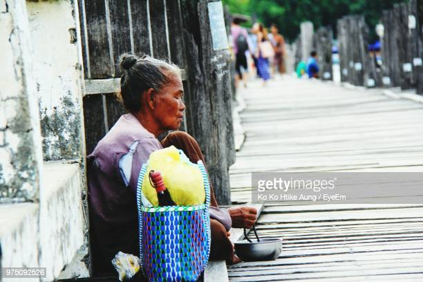 side view of mature woman begging on pier - ko ko htike aung stock pictures, royalty-free photos & images