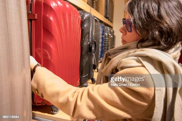 Side View Of Mature Woman Buying Suitcase In Store