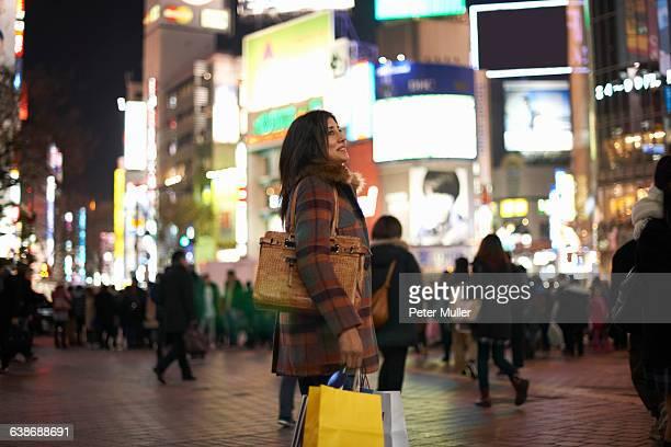Side view of mature woman carrying handbag and shopping bags in city at night looking up smiling, Shibuya, Tokyo, Japan