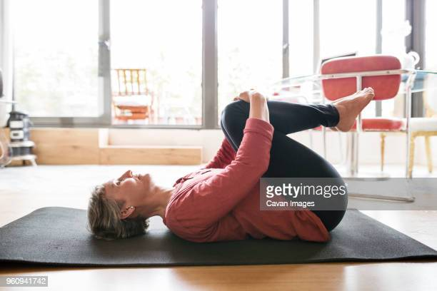 side view of mature woman exercising at home - lying on back stock pictures, royalty-free photos & images