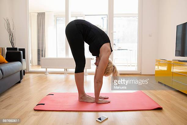 Side view of mature woman in lounge on yoga mat bending over touching floor