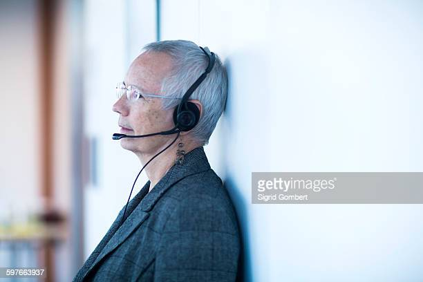 side view of mature woman leaning against wall wearing telephone headset looking away - sigrid gombert stock pictures, royalty-free photos & images